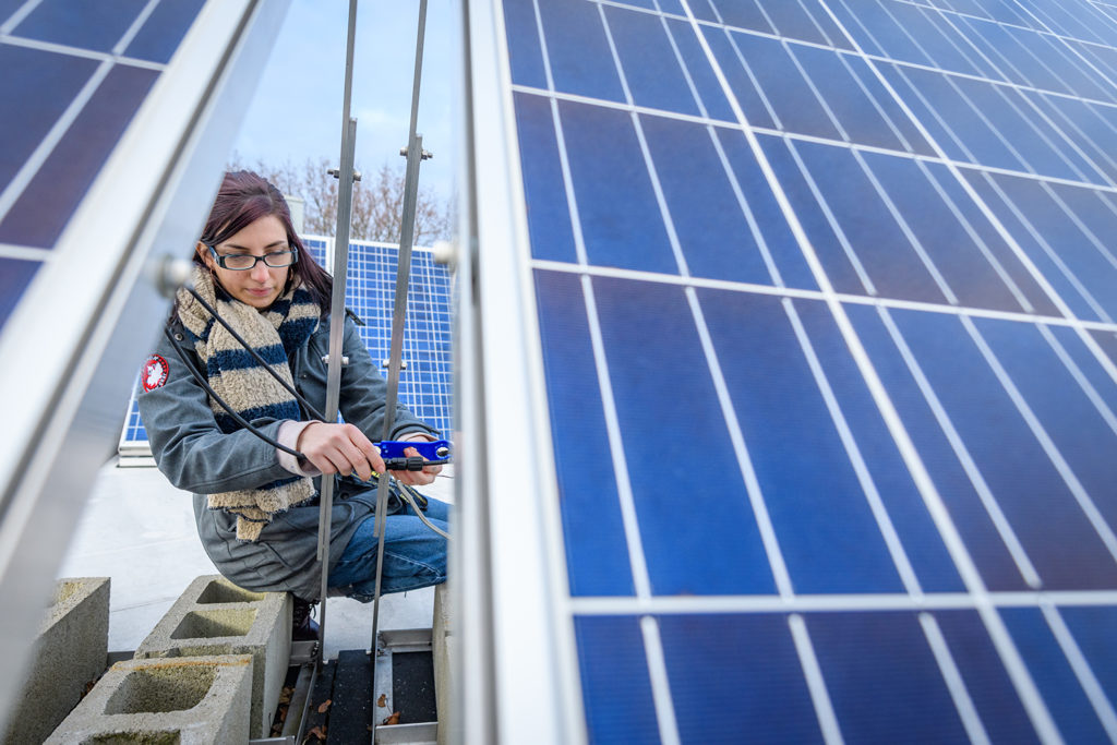 Megan McIntyre works on a solar panel