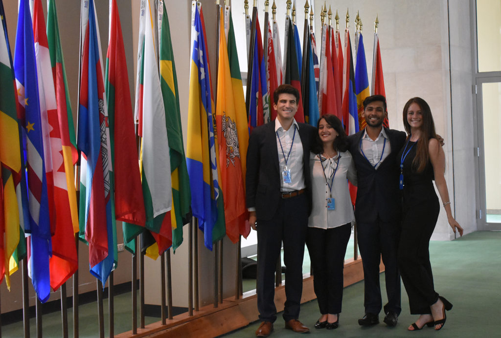 Four students stand in front of flags at United Nations