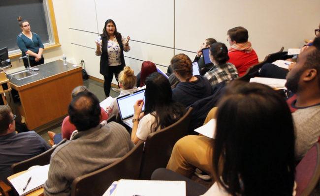 Clark alumni standing in front of class