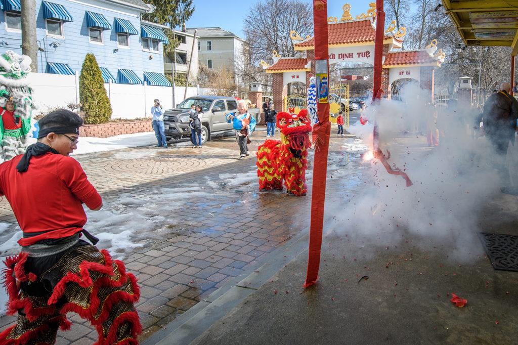Man setting off fireworks on Lunar New Year near Clark campus