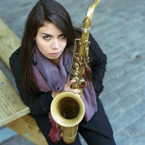 Melissa Aldana holding saxophone