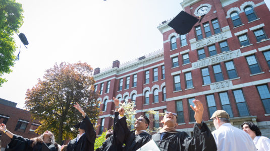 Members of the Clark University Class of 2019 toss their caps after graduation