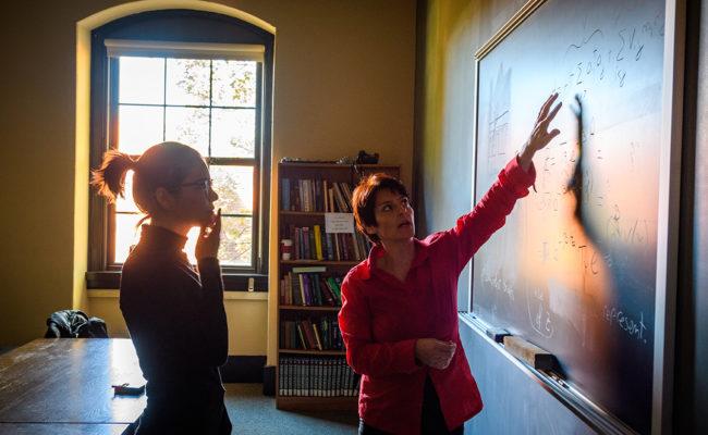 Student and professor at blackboard.