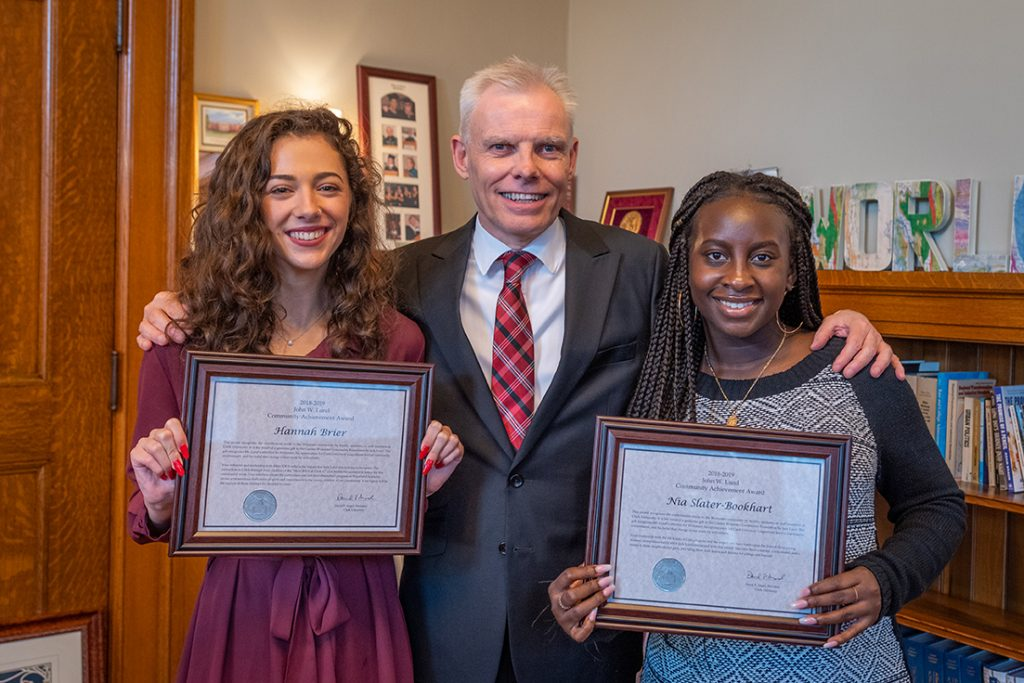 President David Angel presents Lund awards to Hannah Brier '20, left, and Nia Slater-Bookhart '19.