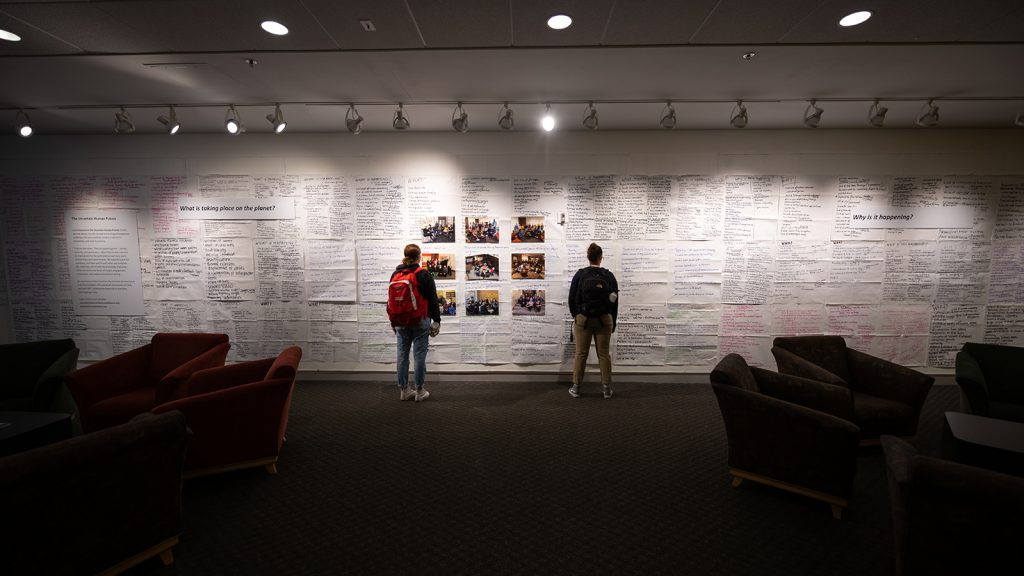 Students view the Council on the Uncertain Human Future exhibit at the Clark University Traina Center