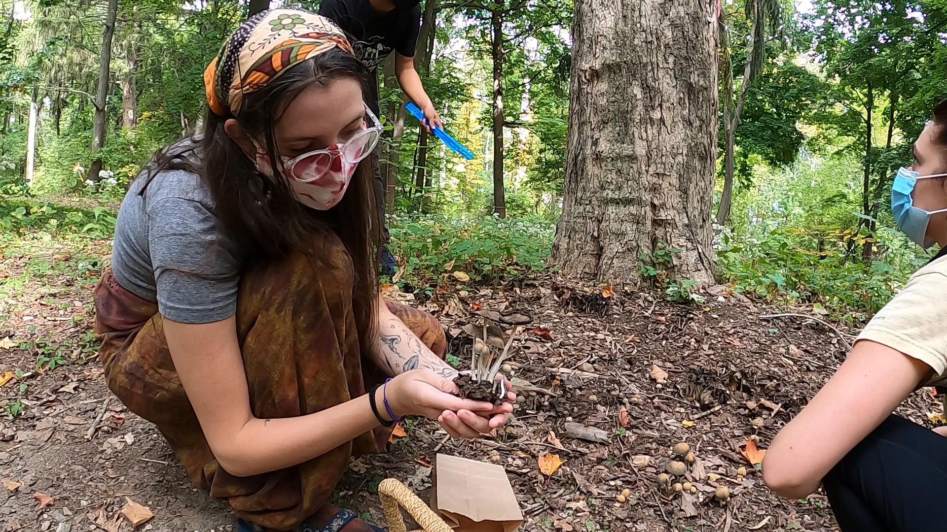 student holding mushrooms