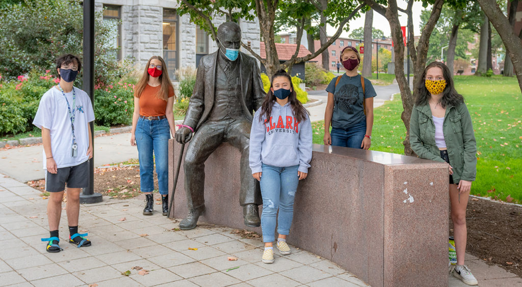 "Students in ""Pandemic: From Horror to Hope"" course stand by the statue of Sigmund Freud on the Clark campus."
