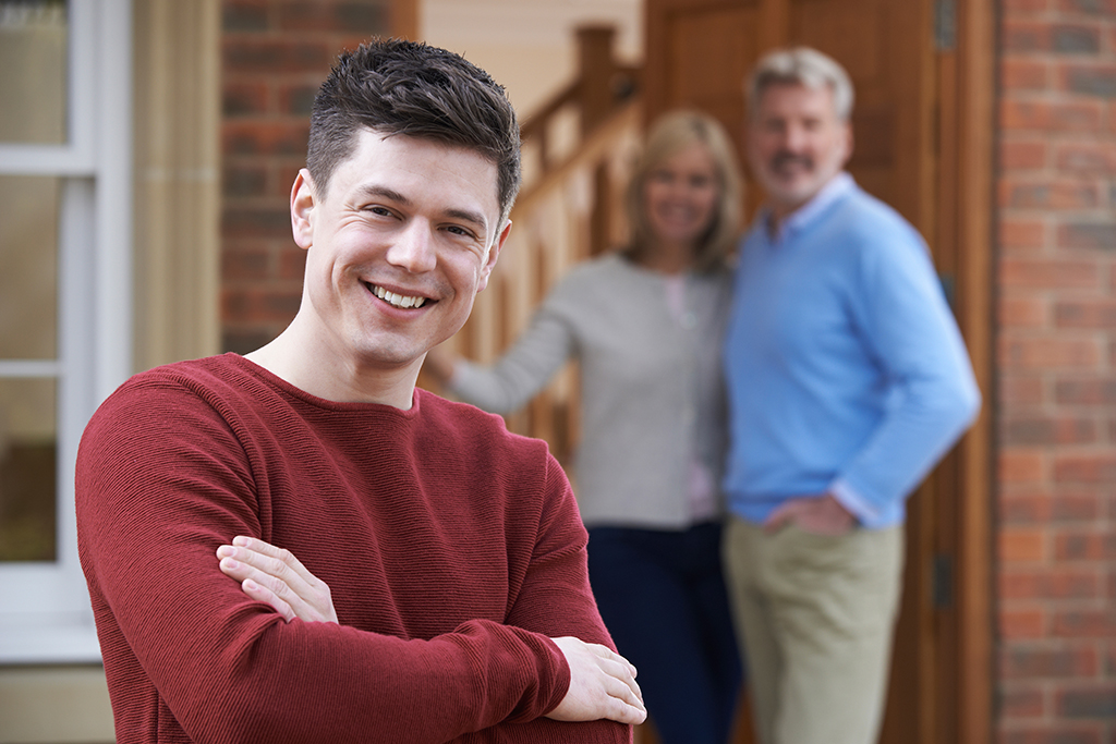 Young man outside house with parents