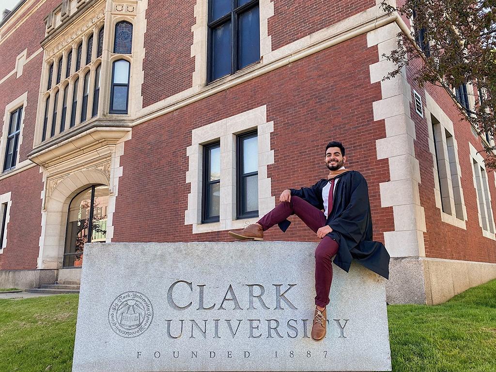 Matheus Gonçalves sits on the Clark University sign outside campus