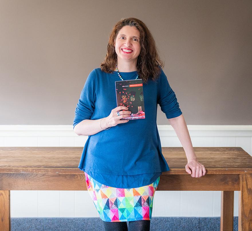 Clark University Professor Belen Atienza holds her collection of poetry