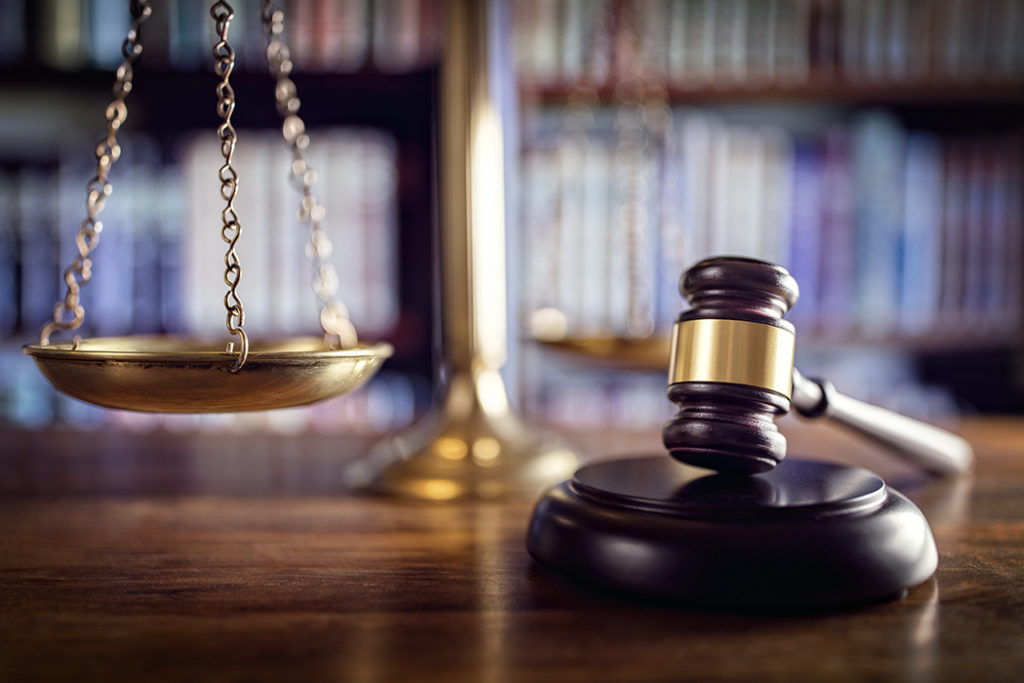 Judge's gavel, scales of justice, and law books in court
