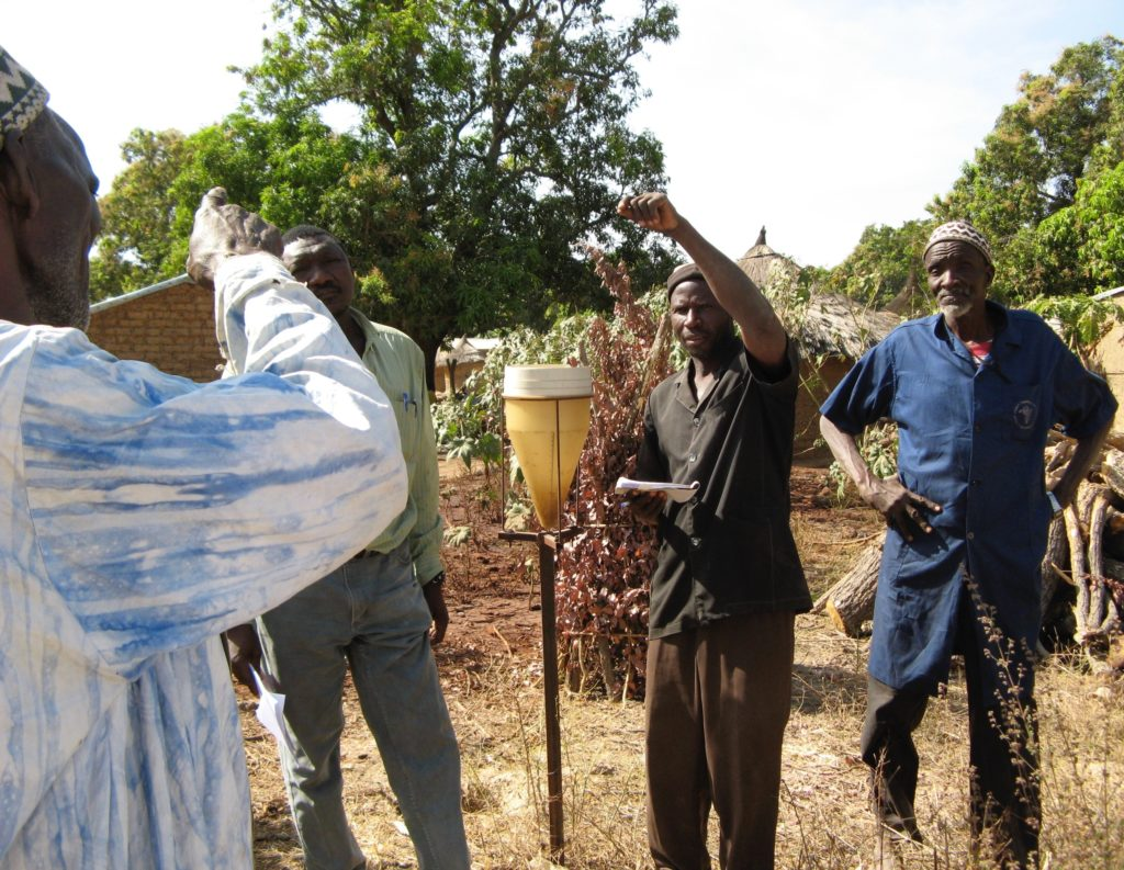 Farmers using rain gauge