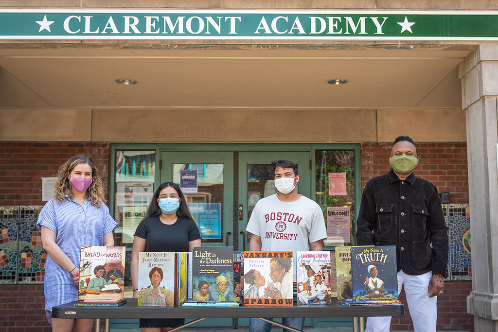 University Park Campus School teacher (and Clark alumna) Helen Ward, Claremont Academy junior Ailany Rivas, UPCS senior Fernando Matos, and Clark professor Raphael Rogers outside the Claremont Academy with some of the books they used in their research on how slavery is represented in schools and children's book publishing.