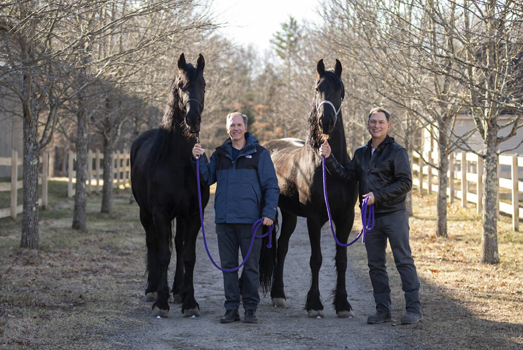 David Fithian and Michael Rodriguez with two of their Fresian horses