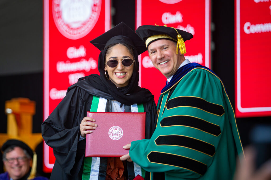 President David Fithian presents a student with a diploma at the 2021 Commencement