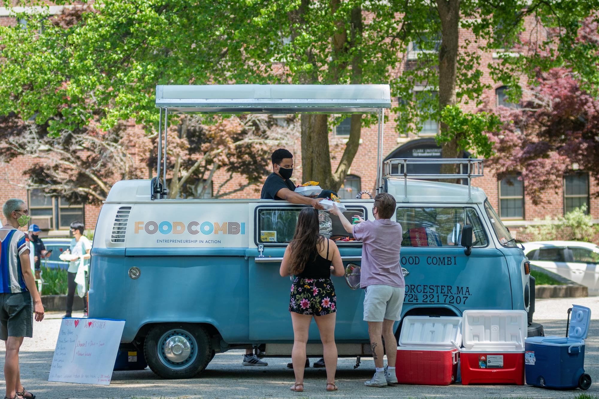 students serve food from a Volkswagen food truck