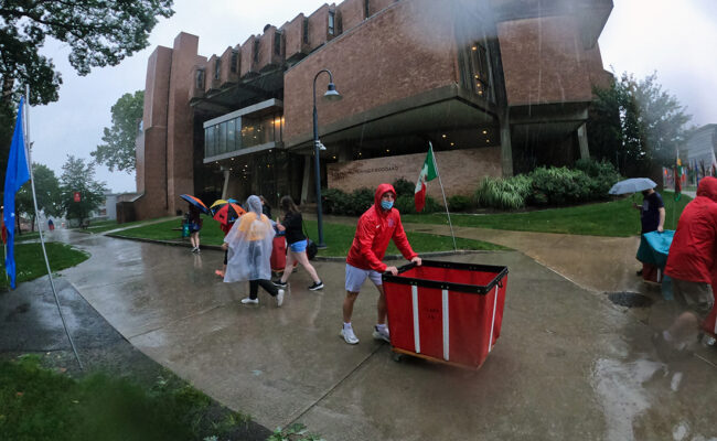 Clark University students on Move-In Day. One student pushes a moving bin.