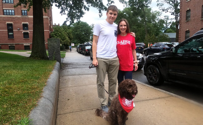 Clark University student and his mother pose with their dog.