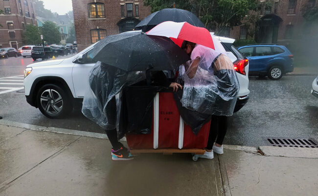 Clark University students huddle under umbrellas while unloading their car during Move-In Day.
