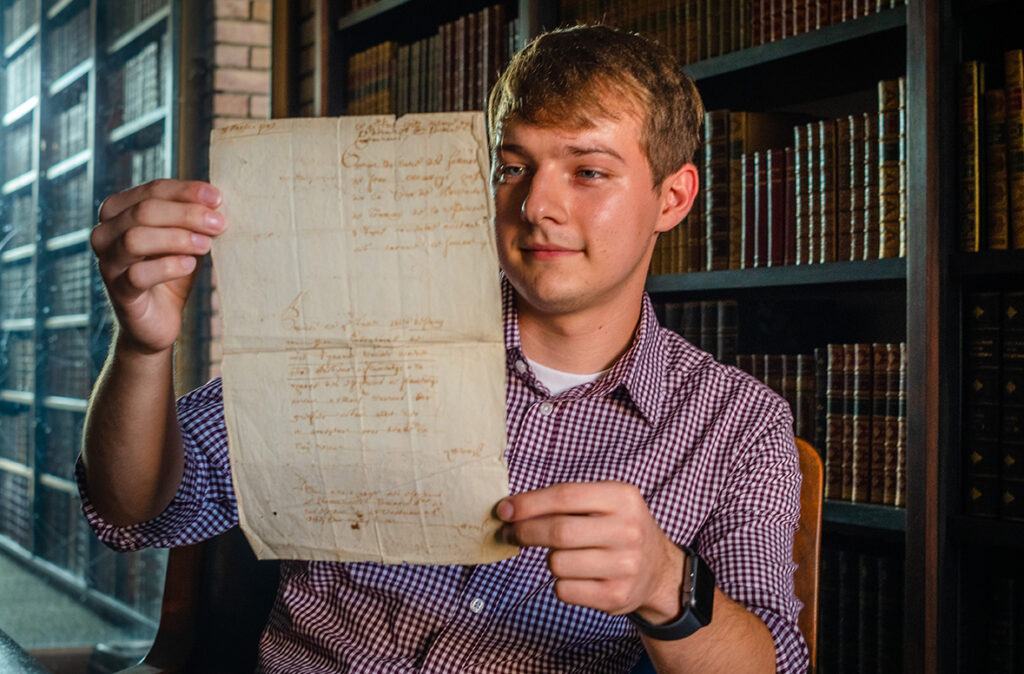 Dillon Prus holds historic Belgian letter found in the Clark University archives.