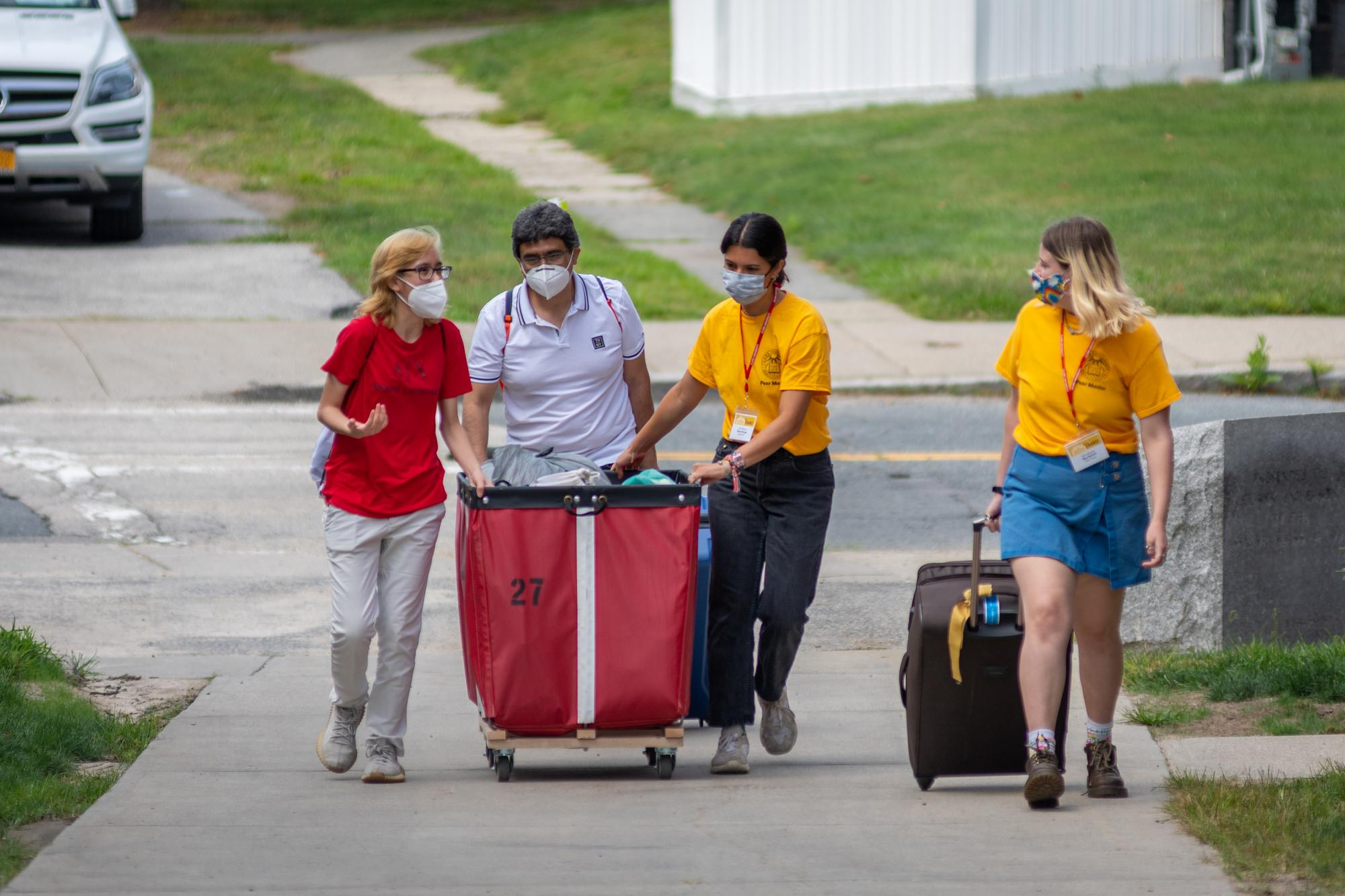 orientation leaders help students with red moving bin move onto campus