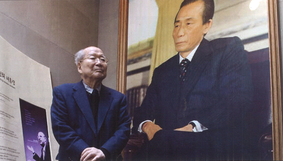 Kim Chung-yum, M.A. '59, LL.D. '95, stands with a portrait of former South Korean President Park Chung Hee at the opening of the Park Chung Hee Memorial-Library in 2012