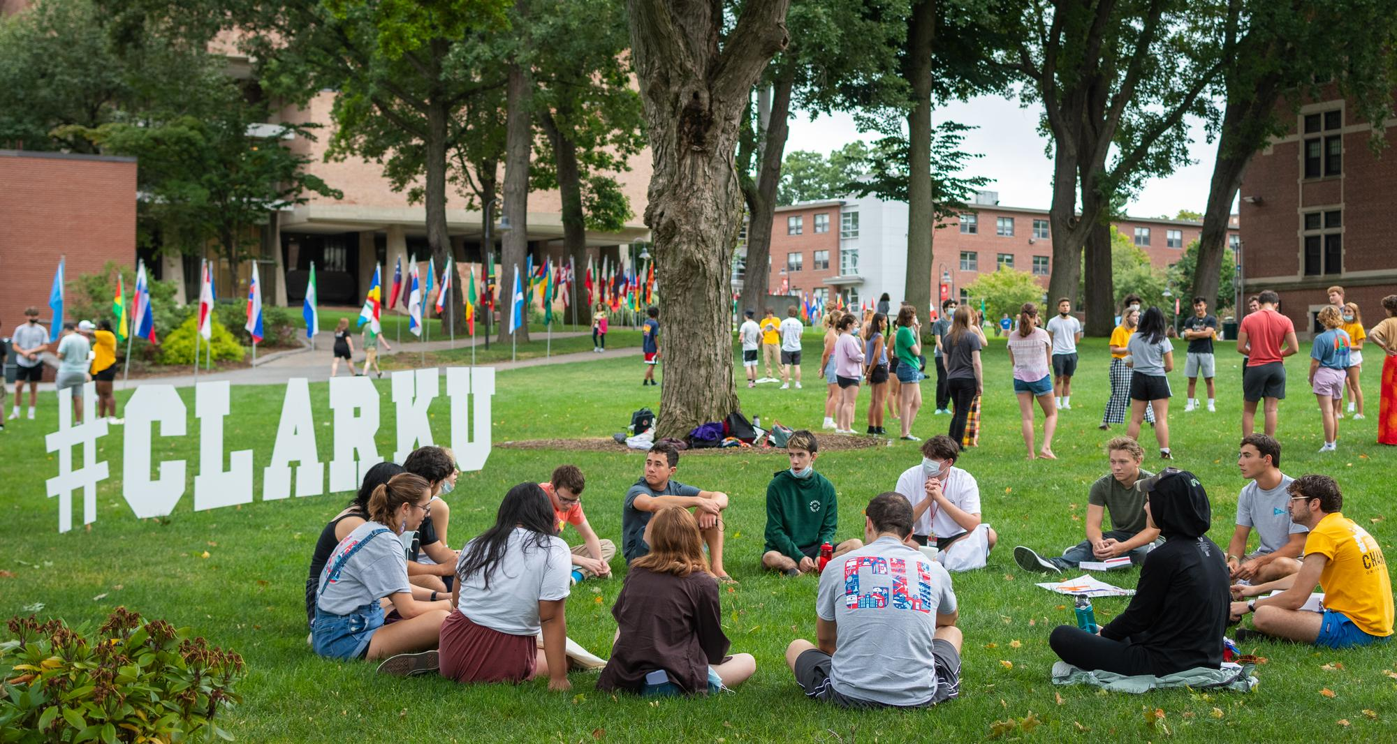 students sit in circle on campus green next to #CLARKU letters