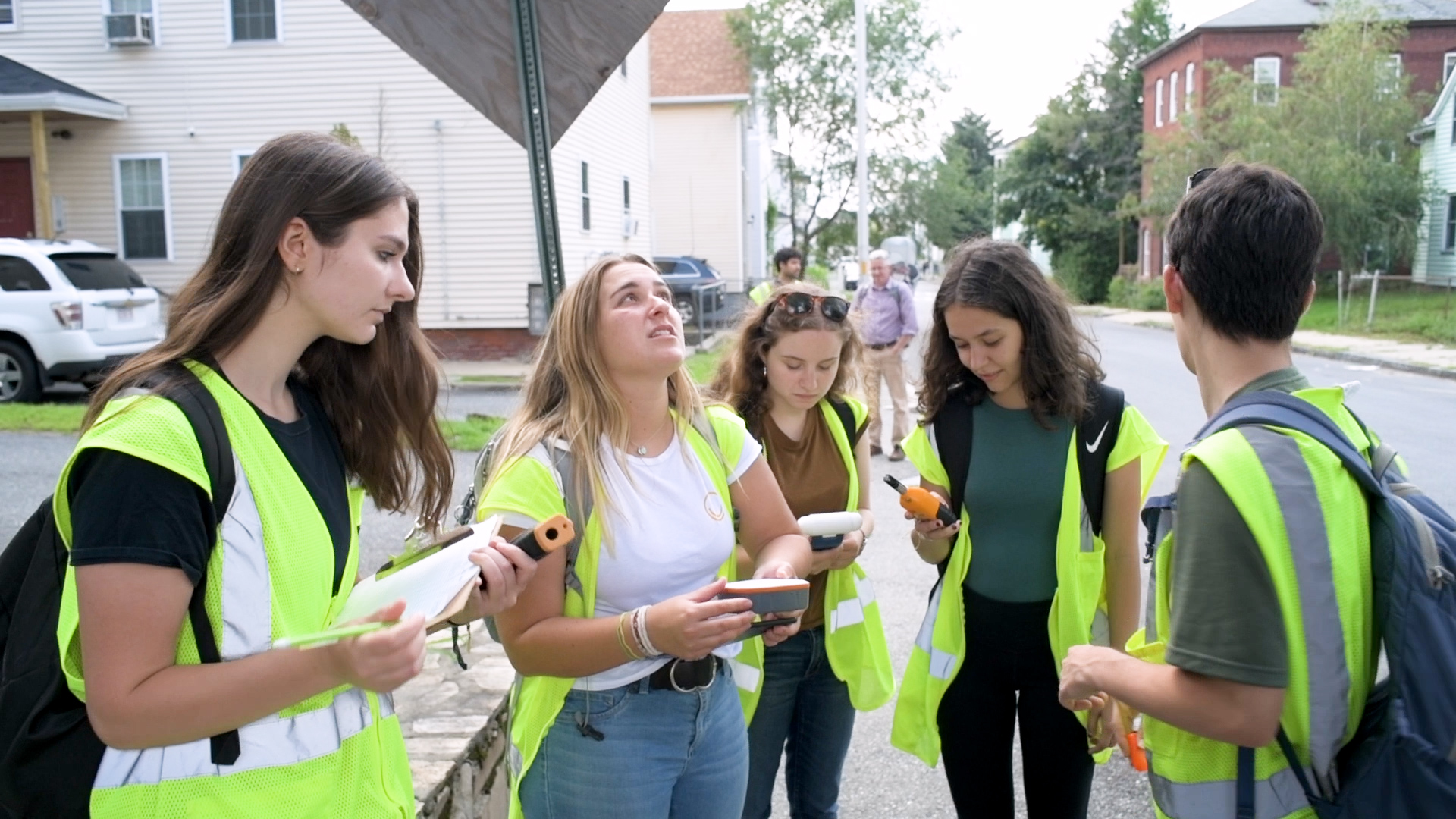five students in green safety vests stand together while conducting research in a Worcester neighborho