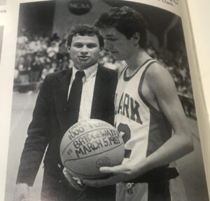 In this photo from the 1983 Clark yearbook, Dan Trant receives the game ball from Wally Halas after scoring his 1,000th career point.