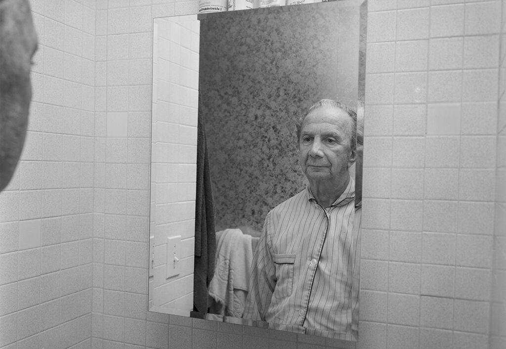 Gene DiRado looks at himself in the mirror