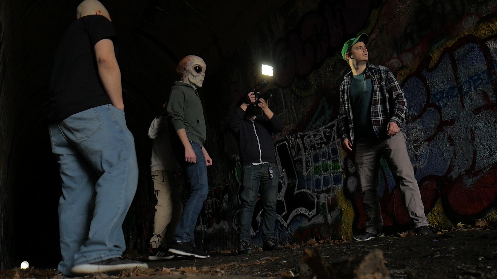 clark alumni film video scene with people in alien masks